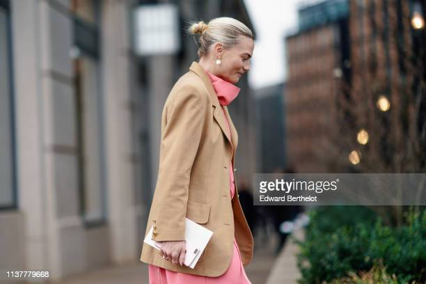 A guest wears a hineck pink dress earrings a camel jacket during London Fashion Week February 2019 on February 16 2019 in London England