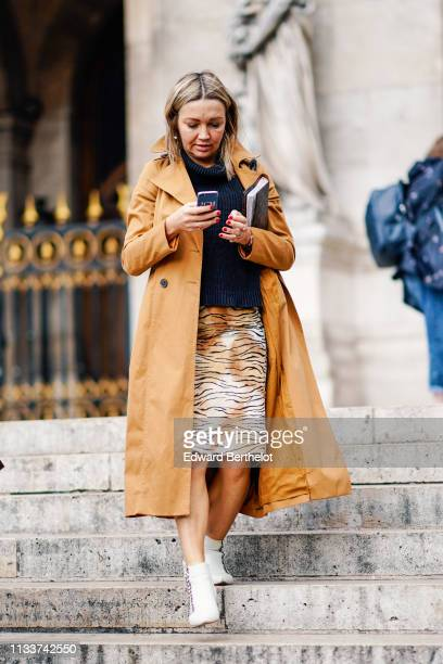 A guest wears a honey color trench coat a black turtleneck a tiger pattern white and camel skirt white ankle boots outside Stella McCartney during...