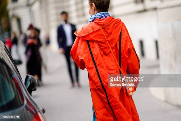 A guest wears a hooded orange coat a blue flower print scarf and an orange and white bag outside Manish Arora during Paris Fashion Week Womenswear...