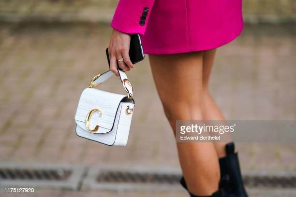 Guest wears a hot pink jacket, a white crocodile pattern Chloe bag, during London Fashion Week September 2019 on September 15, 2019 in London,...