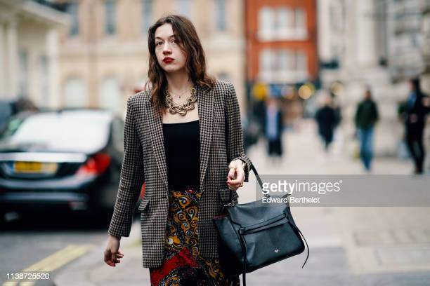 A guest wears a houndstooth jacket a large necklace a black top a black Celine backpack colorful floral print pants during London Fashion Week...