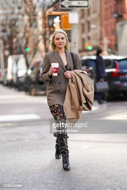A guest wears a houndstooth pattern printed jacket a black mesh floral print skirt black leather boots holds a beige coat during New York Fashion...