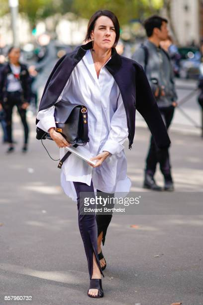 A guest wears a jacket a long blue shirt pants shoes outside Miu Miu during Paris Fashion Week Womenswear Spring/Summer 2018 on October 3 2017 in...