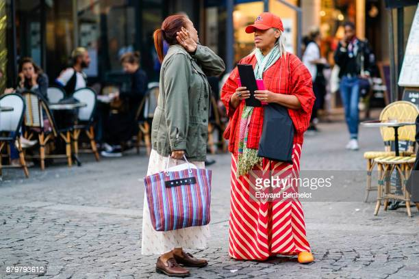 A guest wears a jacket a striped bag brown shoes a guest wears a red cap a red jacket a scarf a striped red dress outside Koche during Paris Fashion...