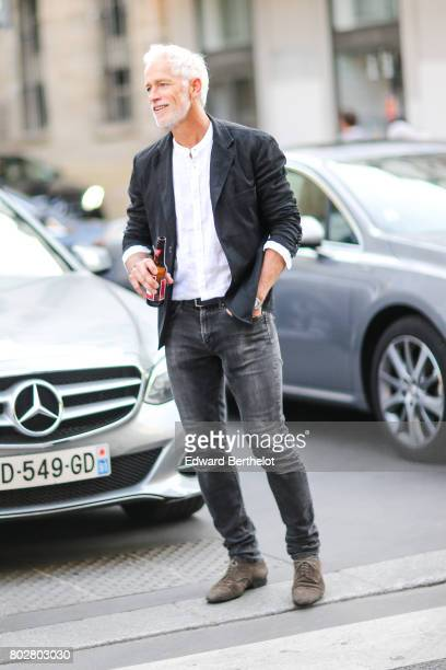A guest wears a jacket a white shirt gray jeans brown suede shoes and is holding a beer bottle outside the Hermes show during Paris Fashion Week...