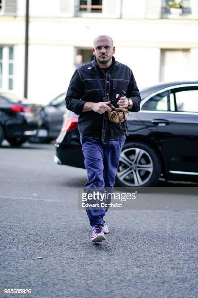A guest wears a jacket blue pants outside 1017 ALYX 9SM during Paris Fashion Week Menswear SpringSummer 2019 on June 24 2018 in Paris France