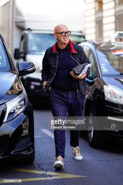 A guest wears a jacket with red inner lining a blue shirt blue pants sneakers a Goyard bag outside Thom Browne during Paris Fashion Week Menswear...