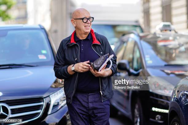 A guest wears a jacket with red inner lining a blue shirt blue pants a Goyard bag outside Thom Browne during Paris Fashion Week Menswear SpringSummer...