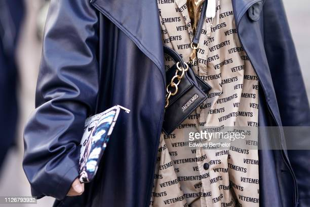 Guest wears a Jacquemus tiny black handbag, a blue leather coat, a beige Vetements dress with words design, during Paris Fashion Week - Menswear F/W...