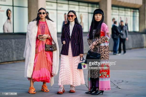 A guest wears a jaguar print coat with pink and red inserts a black turtleneck a jaguar printed pleated side slit dress black thigh high pointy boots...