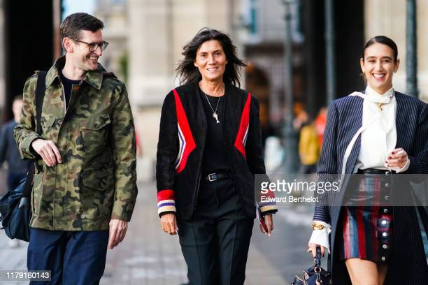 A guest wears a khaki camouflage jacket navy blue pants a black bag Emmanuelle Alt wears necklaces a black top a black jacket with red white and blue...