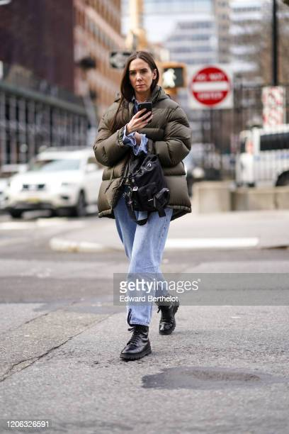 A guest wears a khaki long puffer jacket pale blue denim jeans black leather shoes a bag during New York Fashion Week Fall Winter 2020 on February 12...