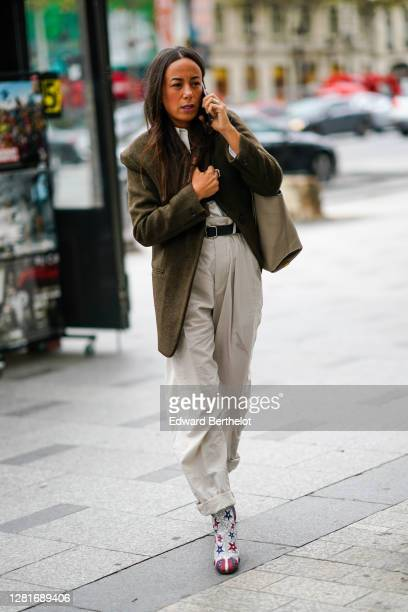 A guest wears a khaki oversized jacket a belt gray cuffed pants star print shoes outside Miu Miu during Paris Fashion Week Womenswear Spring Summer...