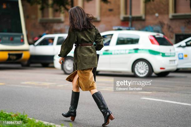 A guest wears a khaki suede jacket a brown crocodile pattern belt a tancolor suede skirt black kneehigh boots outside the Fendi show during Milan...