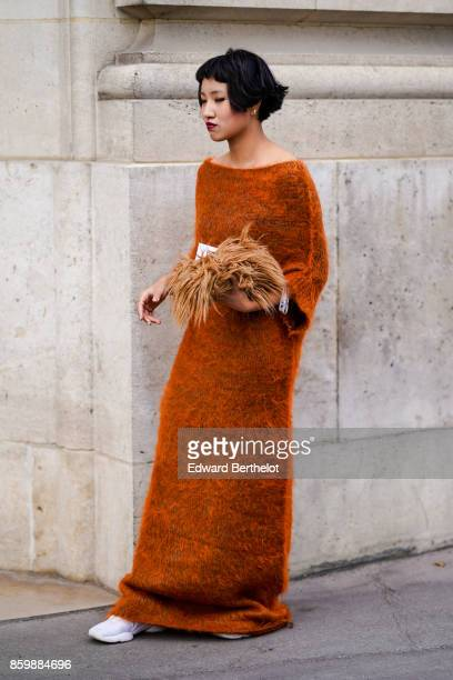 A guest wears a knitted fawncolor long dress with pagoda sleeves white sneakers outside the Rochas show during Paris Fashion Week Womenswear...