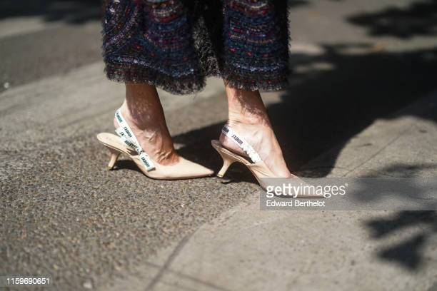 Guest wears a lace and ribbons skirt, beige Dior J'Adior pointy heeled slingback pumps, outside Dior, during Paris Fashion Week -Haute Couture...