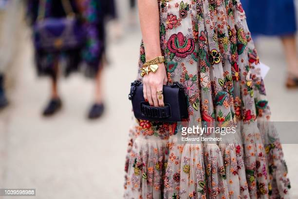 A guest wears a lace dress with embroidered colored flowers a black J'Adior bag outside Dior during Paris Fashion Week Womenswear Spring/Summer 2019...