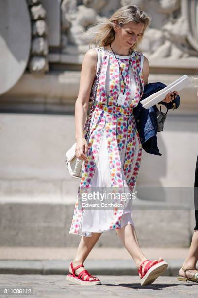 A guest wears a lace ruffle dress with multi color dots red straps sandals a white bag outside the Chanel show during Paris Fashion Week Haute...