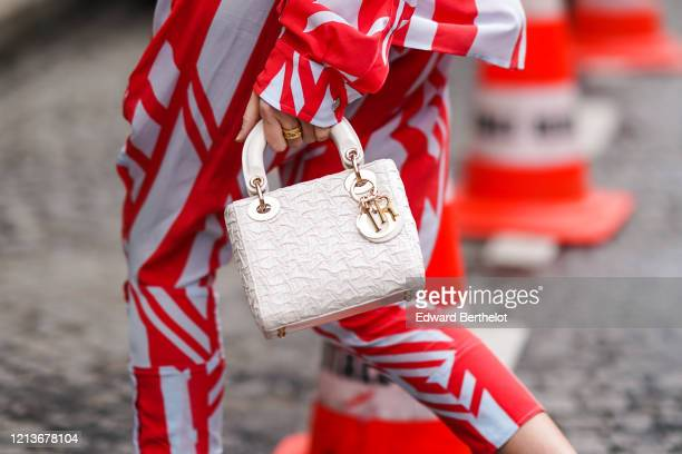 Guest wears a Lady Dior bag, a red and white striped outfit, outside Altuzarra, during Paris Fashion Week - Womenswear Fall/Winter 2020/2021, on...