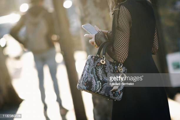 A guest wears a Lady Dior bag with colored embroidery a black dress with fishnet sleeves outside Dior during Paris Fashion Week Womenswear...