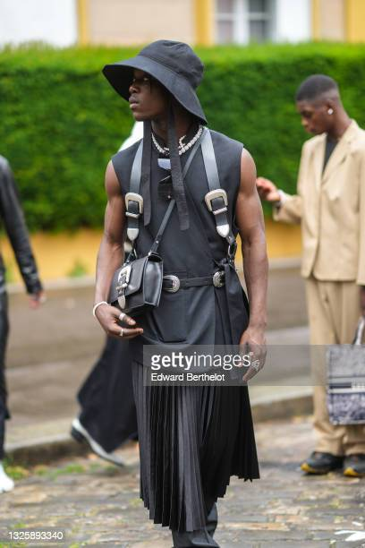 Guest wears a large black bob hat, a white pearls necklace, black sunglasses, a black oversized long sleeveless blazer jacket, a black shiny leather...