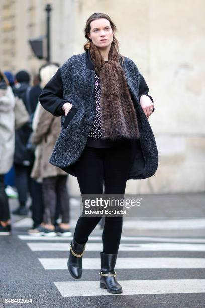 A guest wears a large brown scarf a gray coat black pants and black boots outside the JOUR/NE show during Paris Fashion Week Womenswear Fall/Winter...