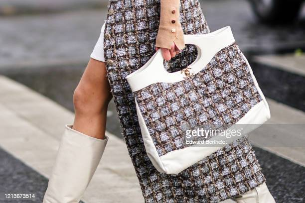 Guest wears a large Chanel bag with woven tweed, a white handle and a golden logo, outside Rokh, during Paris Fashion Week - Womenswear Fall/Winter...