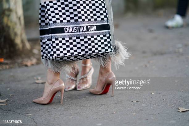 A guest wears a large Christian Dior tote bag pink pointy high heeled pumps from Louboutin outside Koche during Paris Fashion Week Womenswear...