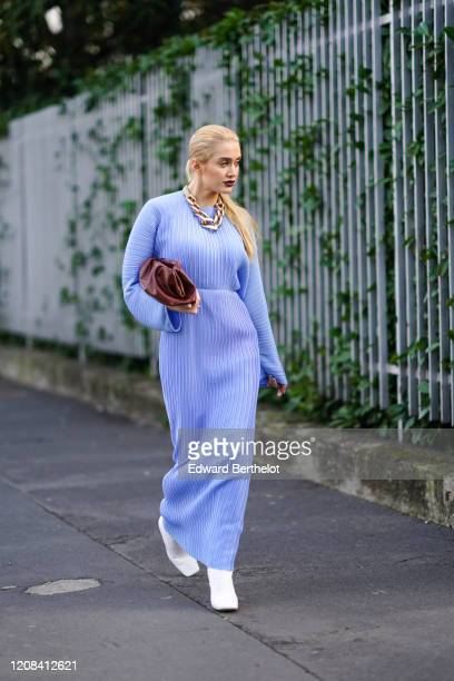 Guest wears a large golden chain necklace, a blue/mauve pleated dress, a brown leather puff bag, white shoes, outside BOSS, during Milan Fashion Week...