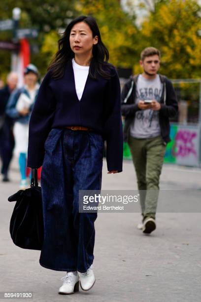A guest wears a large navy blue Vneck pull over baggy navy blue jeans large black bag and white shoes outside Ann Demeulemeester during Paris Fashion...