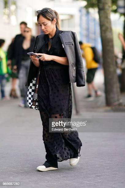 A guest wears a leather jacket a black lace mesh dress outside 1017 ALYX 9SM during Paris Fashion Week Menswear SpringSummer 2019 on June 24 2018 in...