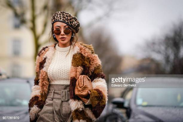 A guest wears a leopard print beret hat a brown fur coat a white wool pull over a skirt during Paris Fashion Week Womenswear Fall/Winter 2018/2019 on...
