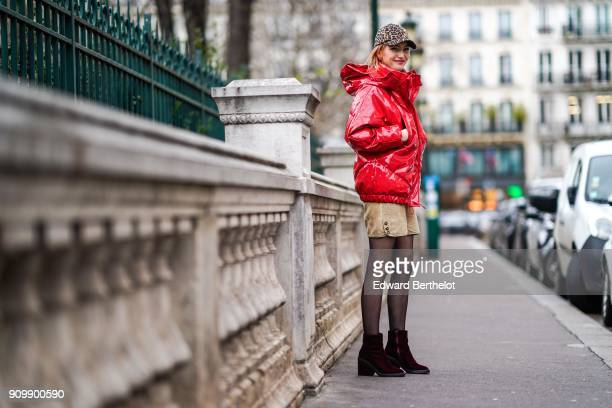 A guest wears a leopard print cap a red puffer coat brown short tights outside Jean Paul Gaultier during Paris Fashion Week Haute Couture...