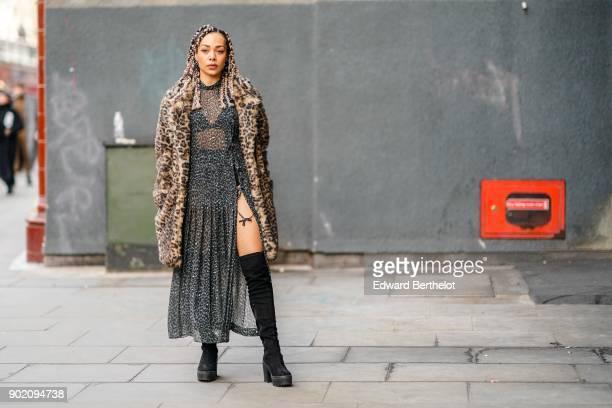 A guest wears a leopard print coat a leopard print transparent dress black bras black thigh high boots during London Fashion Week Men's January 2018...