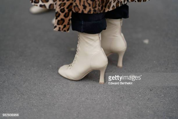 A guest wears a leopard print coat offwhite laceup booties during Paris Fashion Week Womenswear Fall/Winter 2018/2019 on March 3 2018 in Paris France