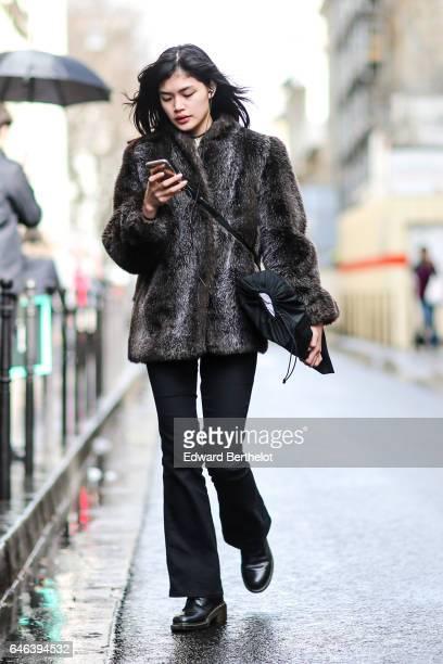 A guest wears a leopard print fur coat a black bag black pants and black shoes outside the JOUR/NE show during Paris Fashion Week Womenswear...