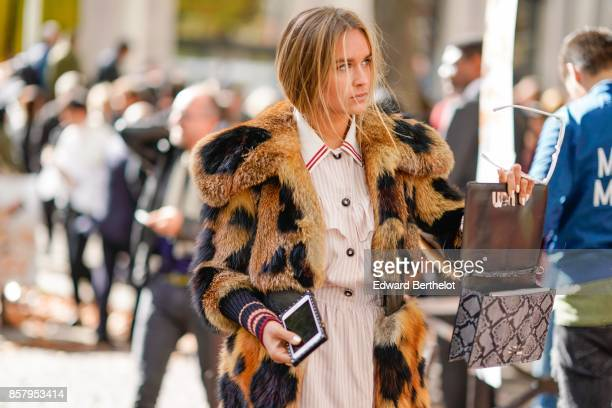 A guest wears a leopard print fur coat a white dress a snake print bag outside Miu Miu during Paris Fashion Week Womenswear Spring/Summer 2018 on...