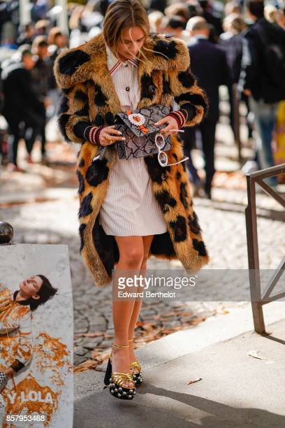 A guest wears a leopard print fur coat a white dress a snake print bag outside Miu Miu during Paris Fashion Week Womenswear Spring/Summer 2018 on...