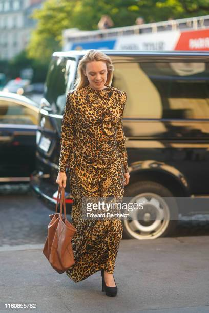 A guest wears a leopard print long dress a lightbrown bag black platform pumps outside Azzaro during Paris Fashion Week Haute Couture Fall/Winter...