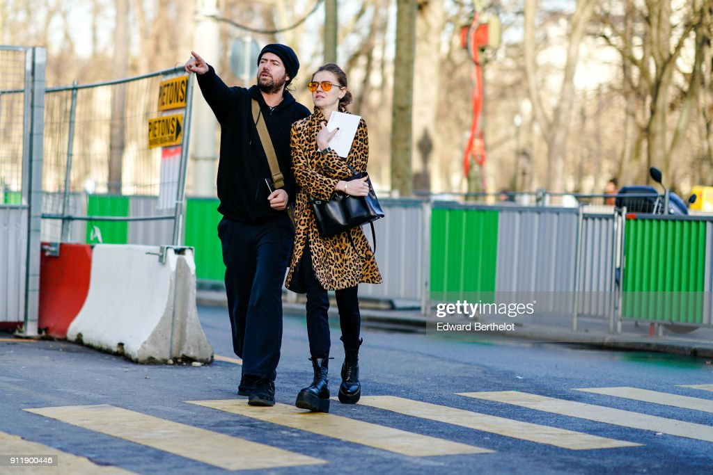 A guest (R) wears a leopard print yellow coat, outside Chanel, during Paris Fashion Week -Haute Couture Spring/Summer 2018, on January 23, 2018 in Paris, France.