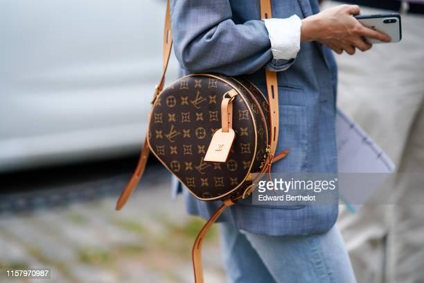 Guest wears a light blue jacket, a Louis Vuitton monogram bag, outside Hermes, during Paris Fashion Week - Menswear Spring/Summer 2020, on June 22,...