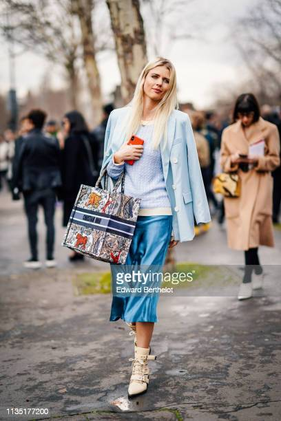 A guest wears a light blue jacket a white trimmed light blue sweater a multicolor animal print Dior tote bag a shiny blue skirt beige ankle boots...
