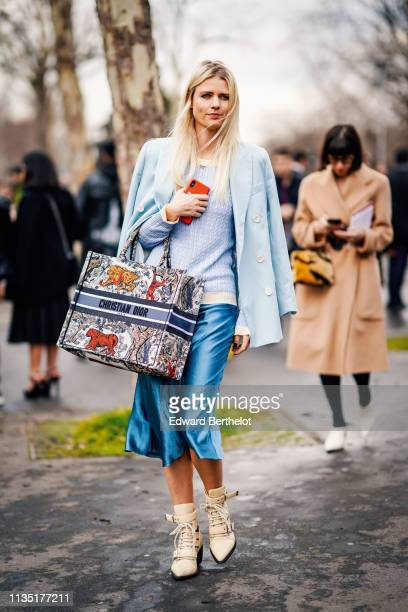 Guest wears a light blue jacket, a white trimmed light blue sweater, a multicolor animal print Dior tote bag, a shiny blue skirt, beige ankle boots,...