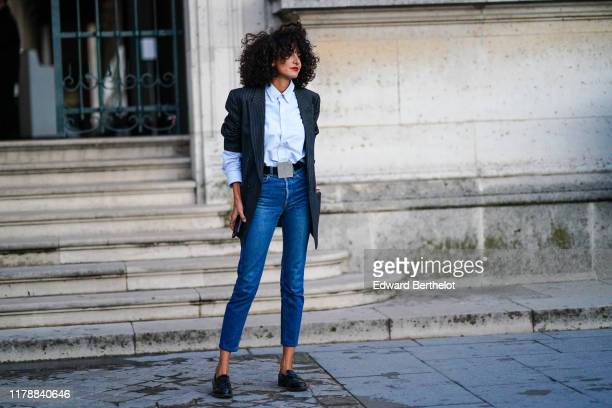Guest wears a light blue shirt, a dark grey oversized jacket with thin white stripes, a black belt with a large square buckle, blue denim crop pants,...