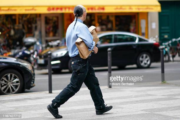 A guest wears a light blue shirt black cargo cuffed pants black sneakers outside White Mountaineering during Paris Fashion Week Menswear...
