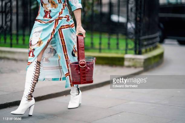 Guest wears a light blue slit dress with brown stripes, a translucent vinyl bucket bag with a brown alligator pattern bag inside, white knee high...
