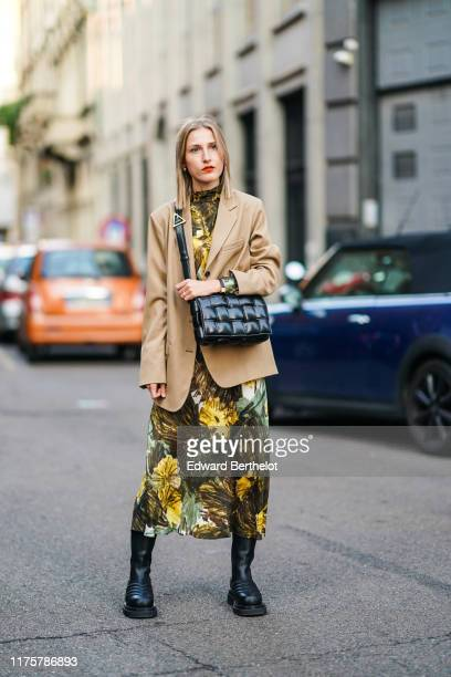 Guest wears a light brown blazer jacket, a black leather quilted bag, a green khaki and yellow floral print dress, black leather boots, outside the...