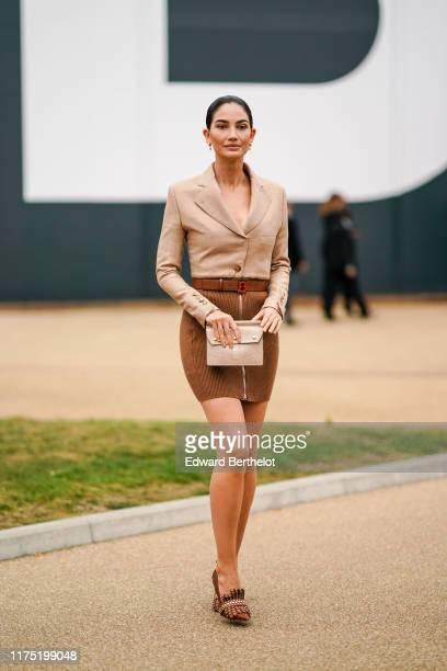 Guest wears a light brown blazer jacket dress with a brown corduroy bottom part, a Burberry belt, a beige clutch, studded moccasins shoes, earrings,,...