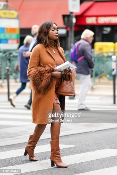 Guest wears a light brown hi-neck top, a tan-color mini skirt, a light brown coat with fur-trimmed cuffs, a tan-color handbag, light brown pointy...