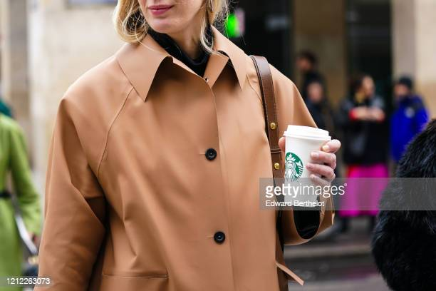 Guest wears a light brown leather coat, holds a coffee cup from Starbucks Coffee, outside Giambattista Valli, during Paris Fashion Week - Womenswear...